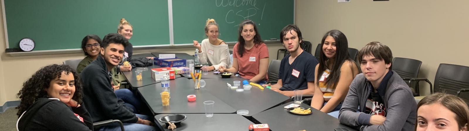 CSP Peer Mentors and Students convene at a table for a meeting